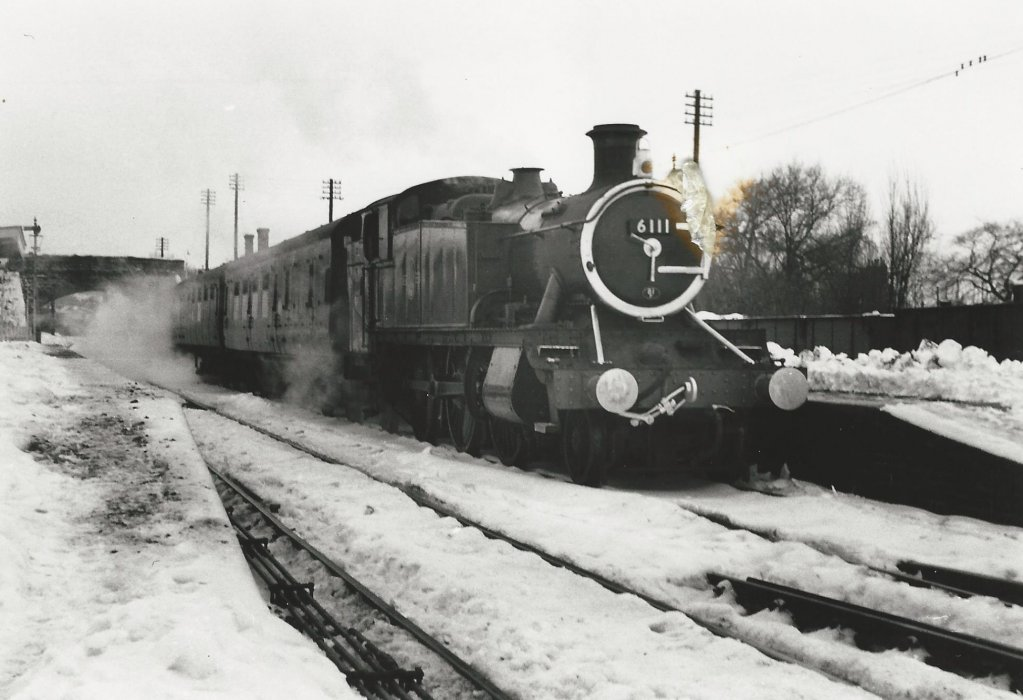 Locomotive 6111 with a passenger train leaving a snowy Wheatley Station