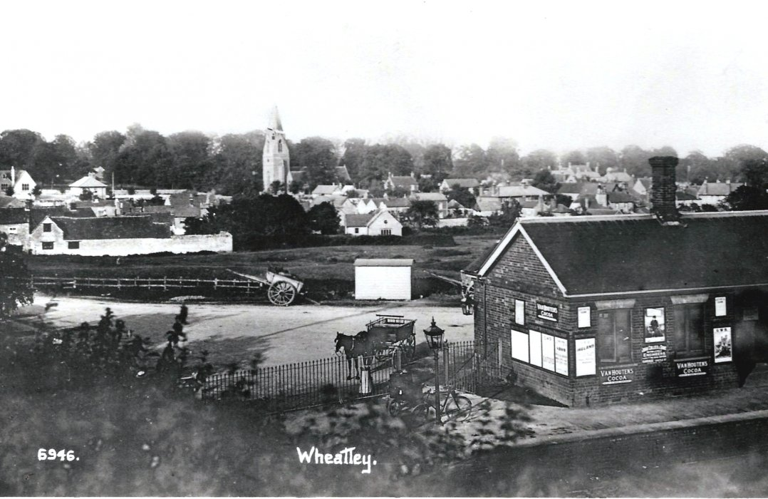 1885. Wheatley station, with village in background. The station building only had one chimney until it was later extended.