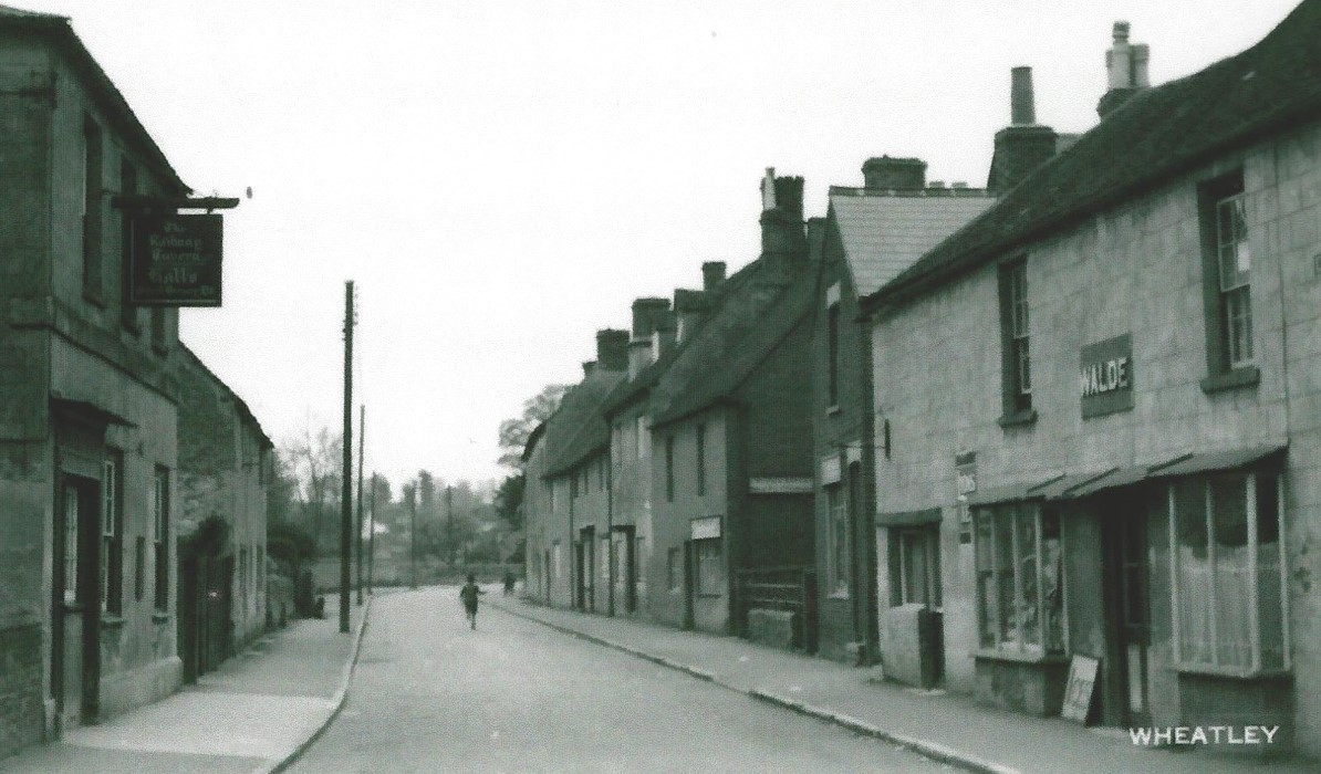 Looking west with the Railway Inn on the left (south) and 'Walde' shop on the right. Peter Bradbury (son of Ronald Bradbury) is trying to fly his kite c. 1949 aged 9.