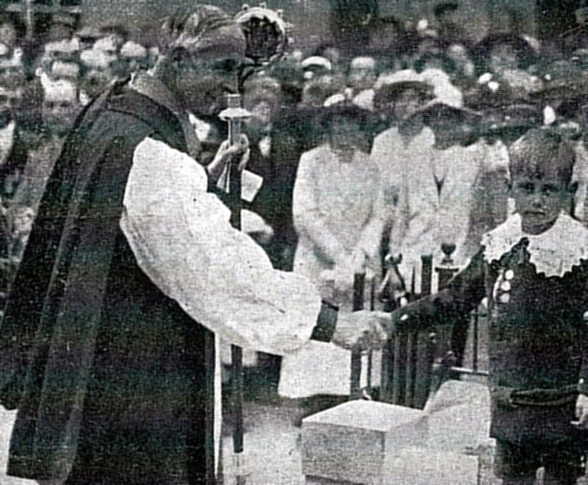 Bishop of Oxford shaking hands with Frederick Harding, a 6-year old orphan, who assisted in the unveiling.