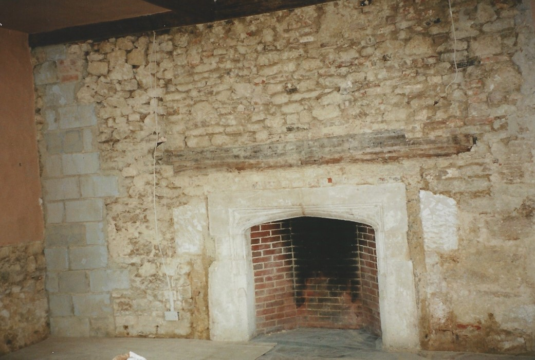 Stone wall and original beam to the fireplace exposed in the main room