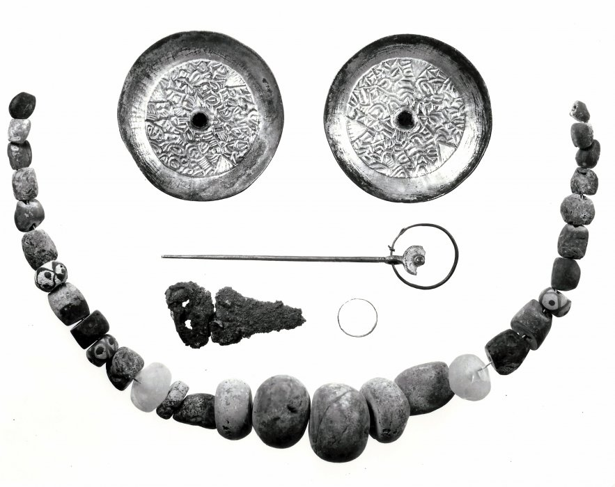 Grave goods from Saxon Grave 14 include two bronze-gilt dish brooches with garnet centres; a silver ring; a 6 inch bronze knife to a bronze buckled belt; a necklace of 25 amber beads; three glass and two crystal beads; and a Celtic silver ring pin
